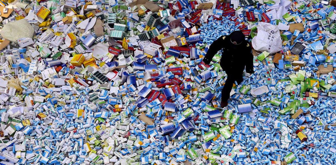 Un policier chinois marche sur un tas de médicaments contrefaits saisis en 2015.